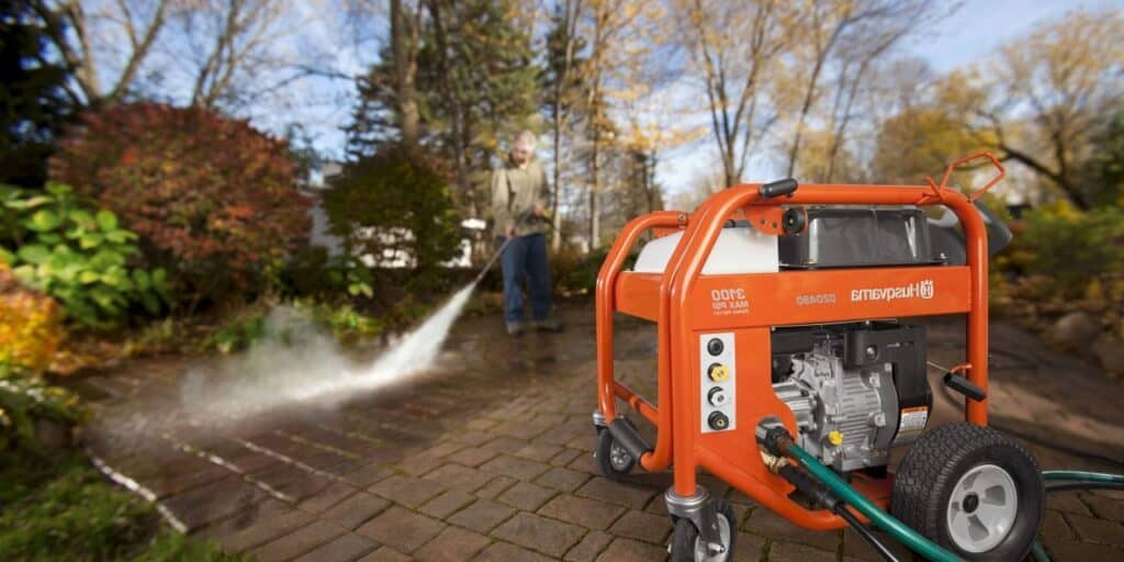 Douglas washes the yard with his new gas pressure washer.