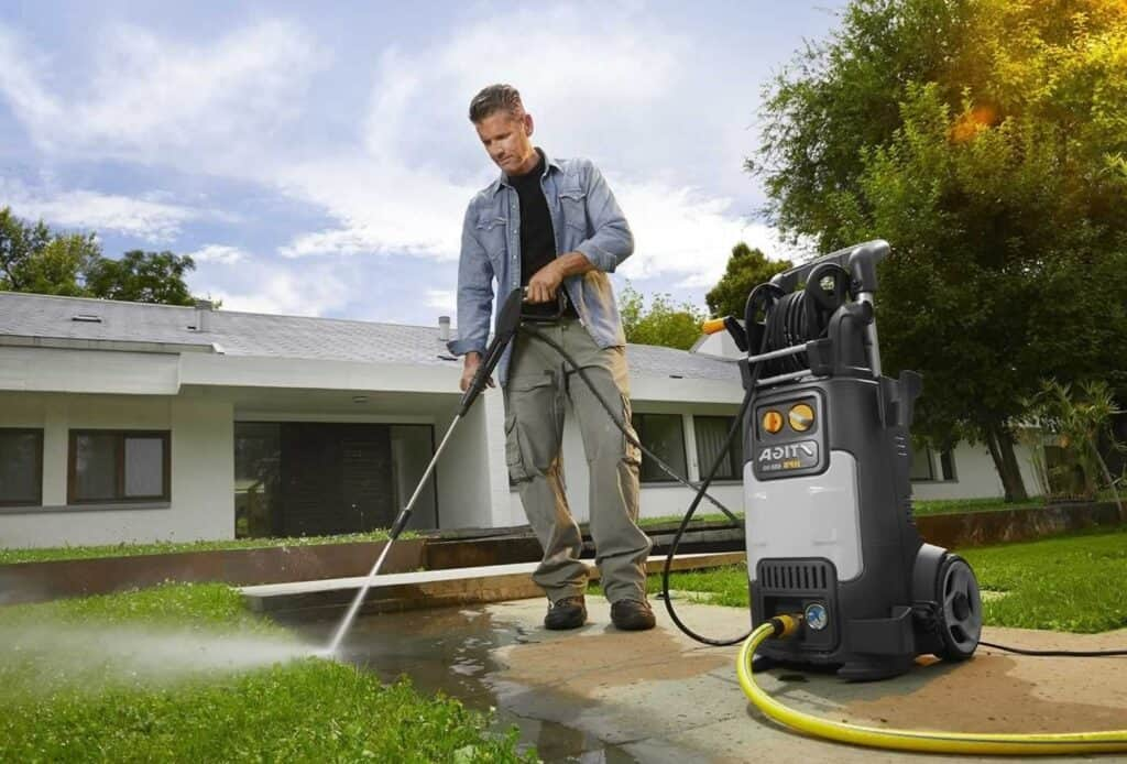 Larry cleans the front of the house with his pressure washer.